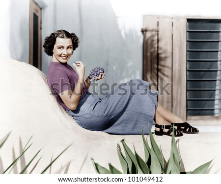 Young woman sitting on a terrace smiling and eating grapes - stock photo