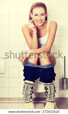 Young woman sitting on a toilet - stock photo