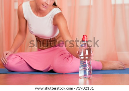 Young woman sitting on a yoga mat and holding bottle of water - stock photo