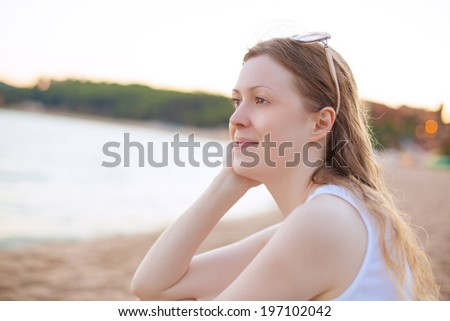 Young woman sitting on beach. - stock photo