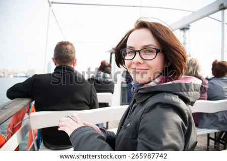Young woman sitting on boat, looking at camera and smiling - stock photo