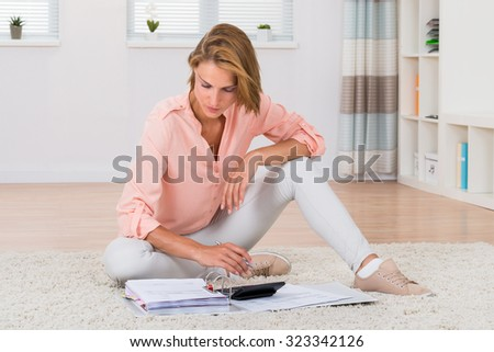 Young Woman Sitting On Carpet Calculating Invoices With Calculator