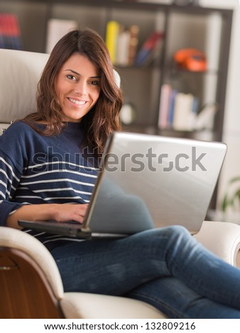 Young Woman Sitting On Chair And Using Laptop, Indoors - stock photo