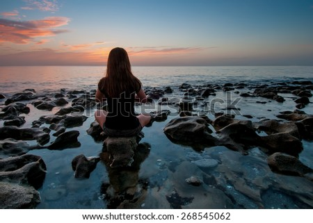young woman sitting on coral rock at calm atlantic ocean sunrise - stock photo