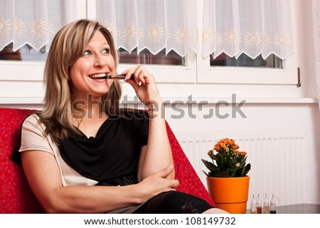 young woman sitting on couch and evaporated E cigarette - stock photo