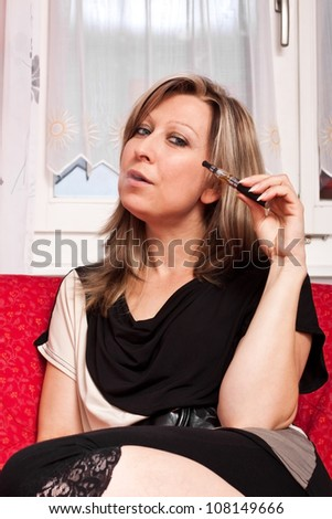 young woman sitting on couch and evaporated electric cigarette - stock photo