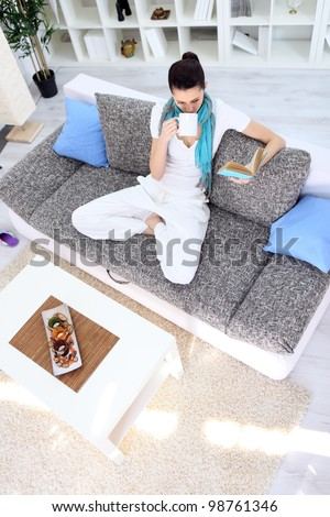 Young woman sitting on couch in living room reading book and drinking tea - stock photo