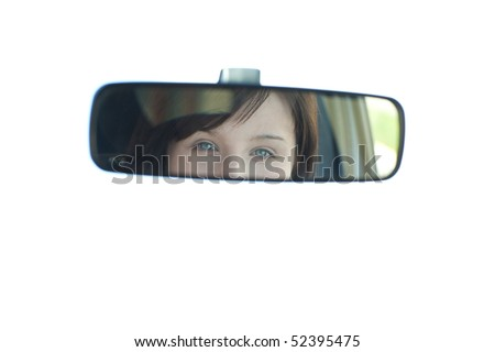 Young woman sitting on driver's seat and looking in the rear-view mirror - stock photo