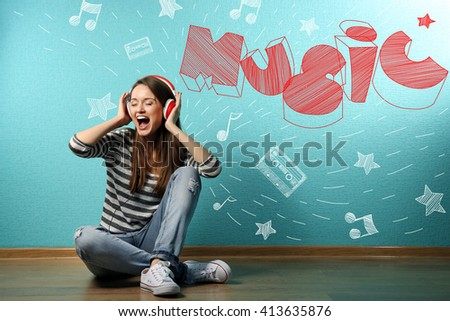 Young woman sitting on floor and listening to music against blue wall - stock photo