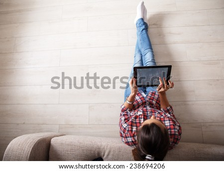 Young woman sitting on floor and using notebook.View from above. - stock photo