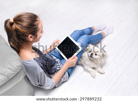 Young woman sitting on floor and using tablet . - stock photo