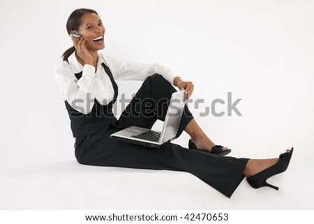 Young woman sitting on floor using laptop and wearing wireless headset. Horizontally format.