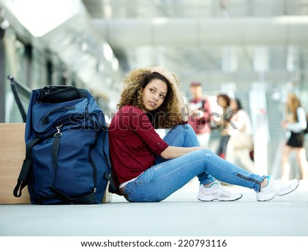 Young woman sitting on floor with luggage at airport - stock photo