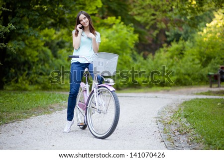 Young woman sitting on her bicycle and talking on the phone - stock photo