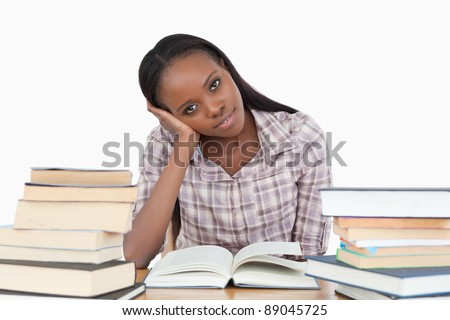 Young woman sitting on her desk with piles of books against a white background