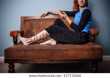 Young woman sitting on old antique sofa holding her phone - stock photo