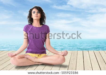 Young woman sitting on pear - stock photo