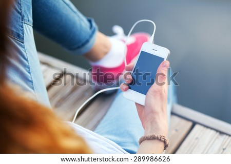 Young woman sitting on pier holding a smartphone. - stock photo
