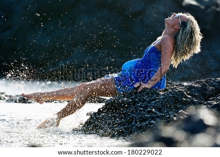 young woman sitting on rocky beach in summer - stock photo