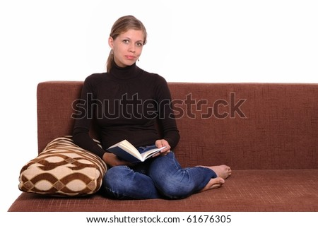 young woman sitting on sofa and thinking with a book in her hands