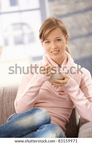 Young woman sitting on sofa at home, eating cereals? - stock photo