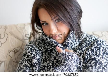 Young woman sitting on sofa in big warm sweater - stock photo