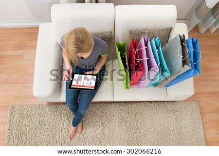 Young Woman Sitting On Sofa With Digital Tablet Shopping Online - stock photo