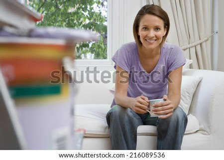 Young woman sitting on sofa with mug, paint pot and brush on ladder in foreground, smiling, portrait (differential focus)