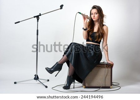 Young woman sitting on speaker and holding microphone in her hand