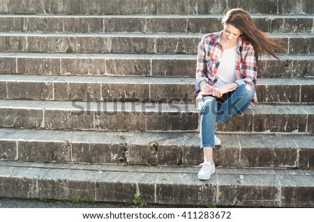 Young woman sitting on stairs in the park and writing on notebook or agenda with copy space - stock photo