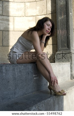 Young woman sitting on stone against wall