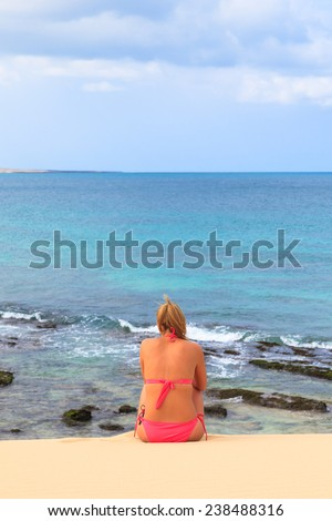 Young woman sitting on the beach looking at the ocean and sky, Boavista - Cape Verde - stock photo