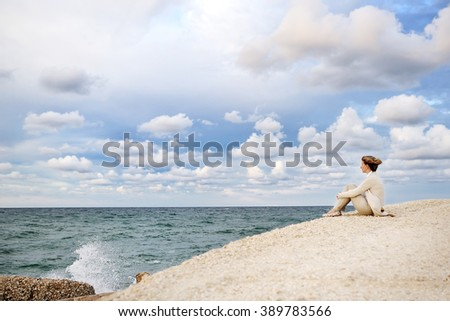 Young woman sitting on the beach looking at the sea and sky - stock photo