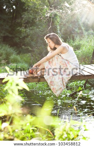 young woman sitting on the bridge in the forest in sunny backlight - stock photo