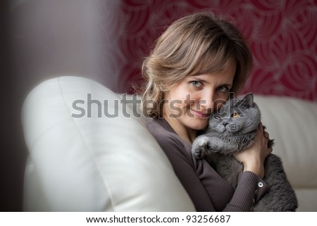 Young woman sitting on the couch and fondles gray cat - stock photo