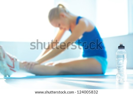 Young woman sitting on the floor after exercise, focus on bottle of water - stock photo