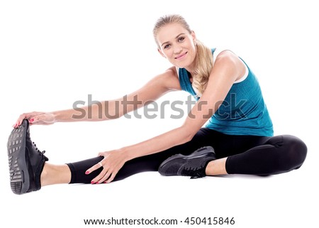 Young woman sitting on the floor and touching her foot. - stock photo