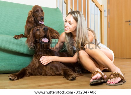 Young woman sitting on the floor next to two purebred dogs in the room - stock photo