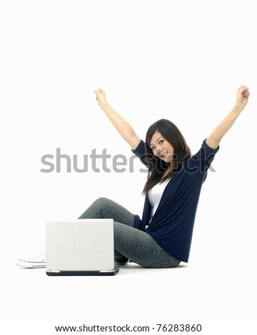 Young woman sitting on the floor with a laptop computer and arms up - stock photo