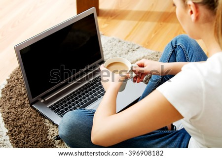 Young woman sitting on the floor with laptop and coffee