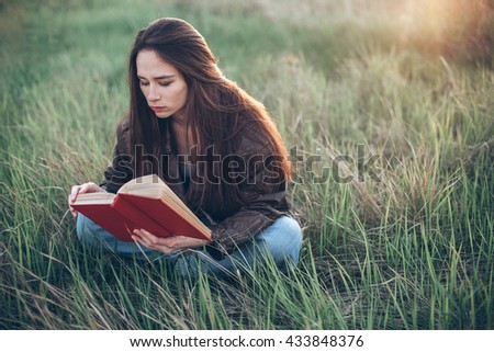 Young woman sitting on the grass and reading a book
