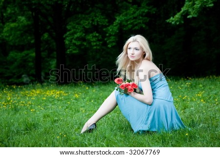 Young Woman Sitting On The Green Grass