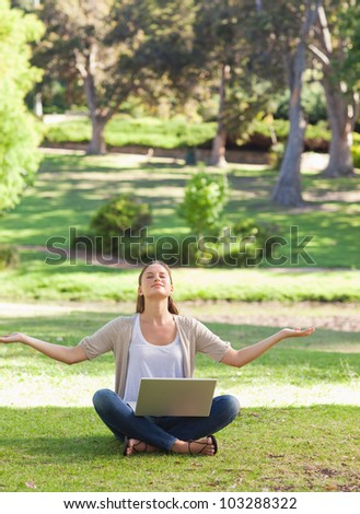 Young woman sitting on the lawn in a yoga position with a laptop - stock photo