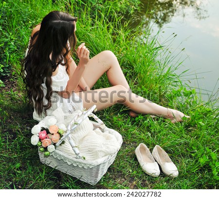 Young woman sitting on the river bank  - stock photo