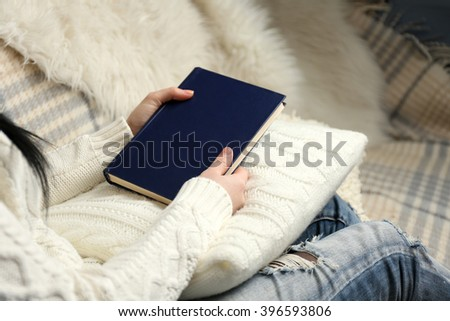 Young woman sitting on the sofa and holding a blue book cover on a white cushion, close up - stock photo