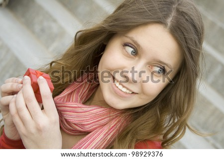Young woman sitting on the stairs to the street, and holds a red gift box