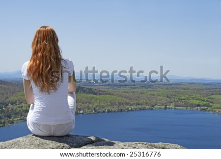 Young woman sitting on top of a mountain, enjoying the view. - stock photo