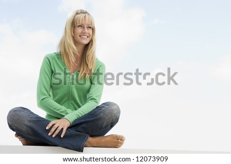 Young woman sitting outside against blue sky