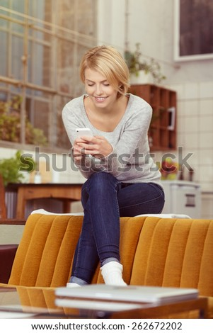 Young woman sitting perched on the top of the sofa at home reading her text messages on her mobile phone with a smile of pleasure - stock photo