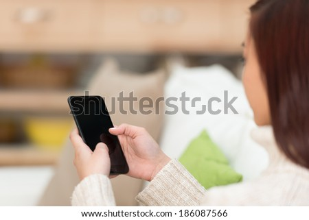 Young woman sitting texting on her smartphone with the blank screen visible to the camera - stock photo